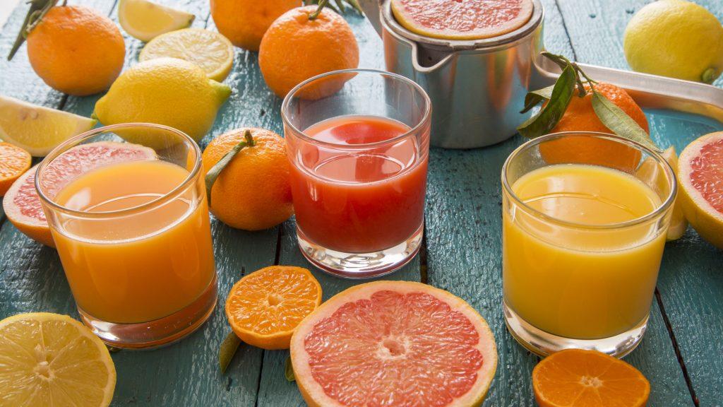 glasses of orange juice grapefruit juice and multivitamine juice juice squeezer and fruits on wood 548008985 571e7ce25f9b58857d2f53cb